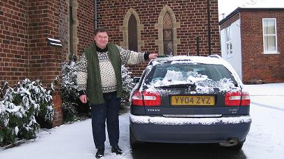 Father James cleaning the snow off his car
